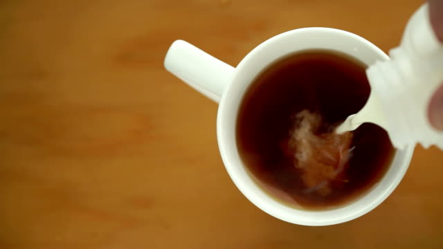 Milk pouring into a hot beverage. video