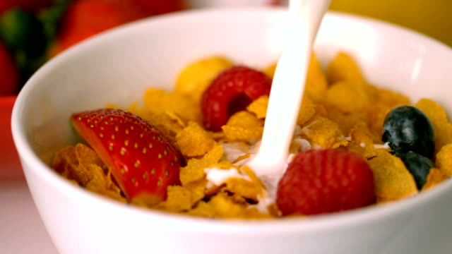 Milk pouring into bowl of cereal with berries video