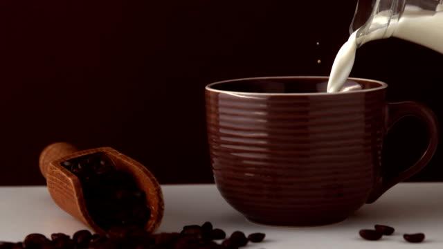 milch gießen in braun kaffee tasse - milchkrug stock-videos und b-roll-filmmaterial
