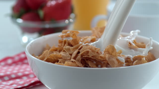 Milk pouring into cereal bowl in slow motion video