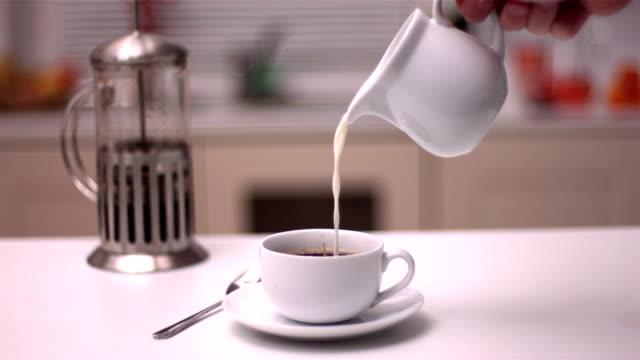 milch in kaffee eingießen - milchkrug stock-videos und b-roll-filmmaterial