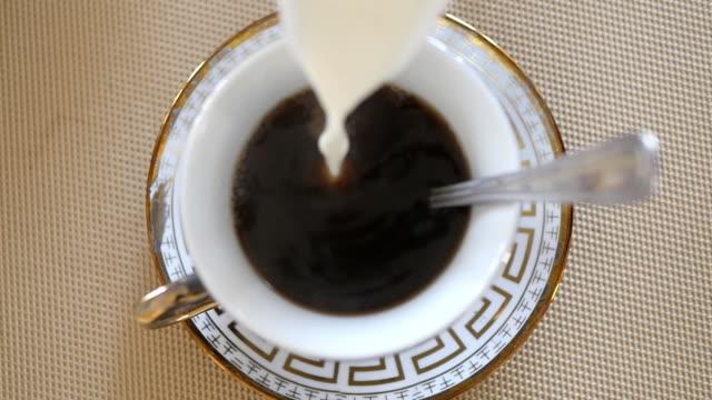 牛乳に紅茶を注ぐします。スローモーションを閉じる - お茶の時間点の映像素材/bロール