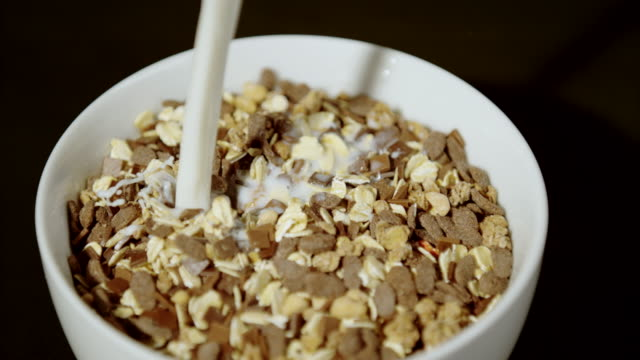 vídeos de stock e filmes b-roll de milk pouring over oats and chocolate flakes, ultra slow motion - oats