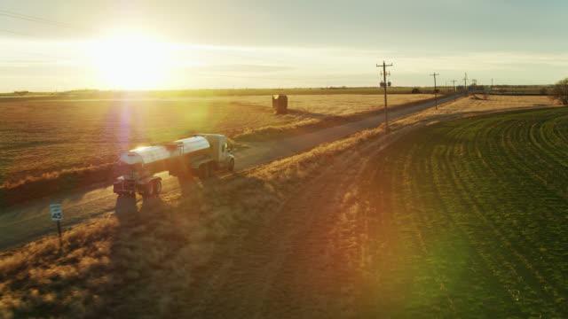 Camion-citerne de lait conduisant à travers des terres agricoles au coucher du soleil - Vidéo