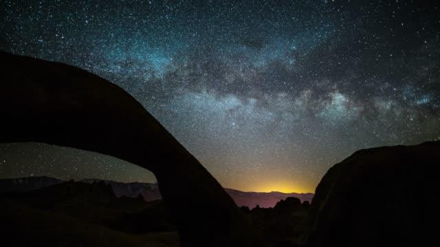 Milky Way over Natural Arch Time lapse shot of night sky with Milky Way moving over the famous Mobius Arch, a natural rock arch, in the Alabama Hills of California. rock formations stock videos & royalty-free footage