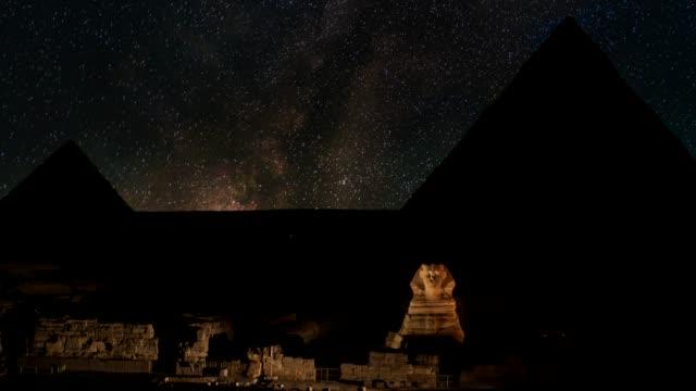 vintergatan över sphinx och pyramider - giza, egypten. - pyramidform bildbanksvideor och videomaterial från bakom kulisserna