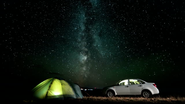 Milky way rotating above camping at night. Slider time lapse video