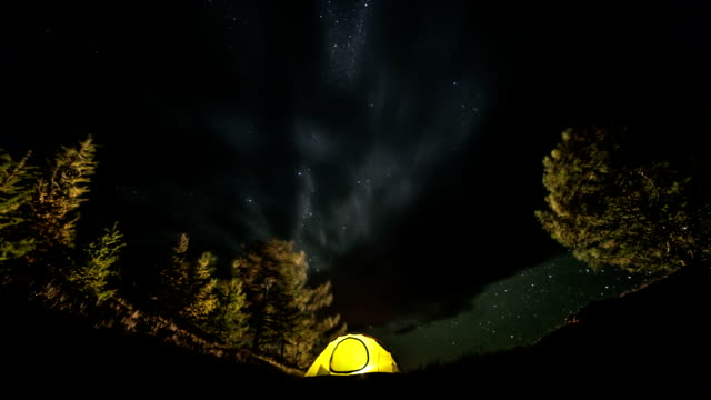 Milky way rotating above tent at night. Slider time lapse video