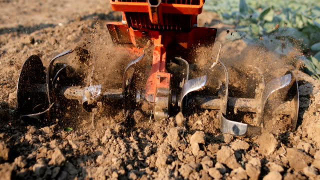 Mill of ploughing tiller in the soil Farmer working in the field. Spring work on the farm. Man plowing the garden harrow agricultural equipment stock videos & royalty-free footage
