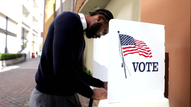 millenial black man voting in election - democrazia video stock e b–roll