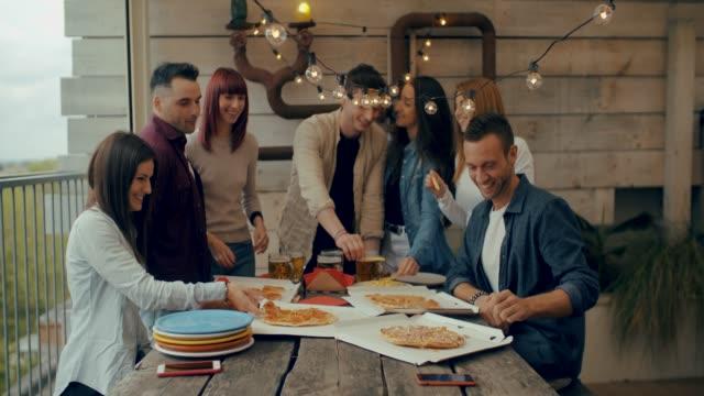 millenial freunde gruppe trinken bier und teilen pizza-scheiben auf dem dach zu hause - freundschaftskonzept mit jungen menschen spaßen zusammen essen snack in risto pub pizzeria. schuss in zeitlupe - brunch stock-videos und b-roll-filmmaterial