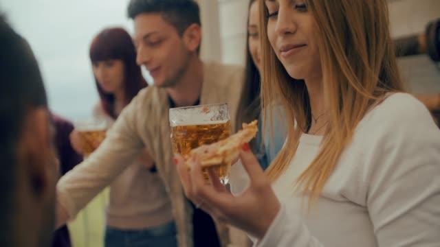 ミレニアル世代の友人グループは、ビールを飲み、自宅で屋上でピザのスライスを共有 - リストパブピッツェリアでスナックを一緒に食べて楽しんでいる若者との友情のコンセプト。スロー� - 食事する点の映像素材/bロール