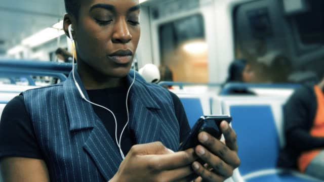 millenial texting while on the train Millenial taking the subway, using her phone to text and listen to music. underground stock videos & royalty-free footage