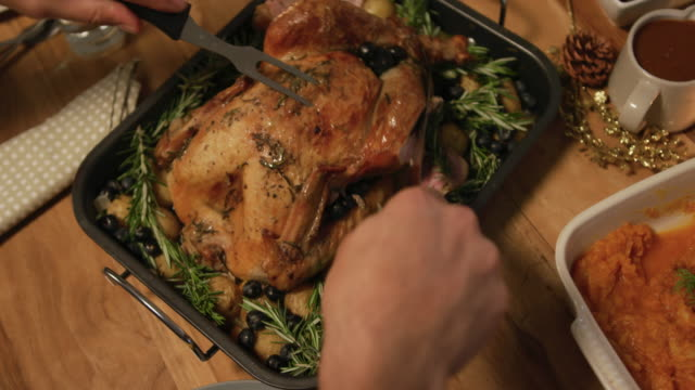 Millennial adult friends celebrating Thanksgiving together at home High angle view of the hands of a young mixed race man sitting at a table for Thanksgiving dinner at home with friends carving the turkey roast dinner stock videos & royalty-free footage