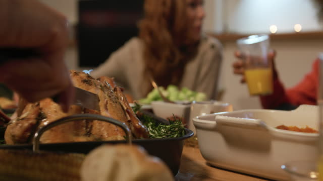 Millennial adult friends celebrating Thanksgiving together at home Low angle close up of the hands of a young mixed race man sitting at a table for Thanksgiving dinner at home with friends carving the turkey, a young Caucasian woman talking at the table in the background roast dinner stock videos & royalty-free footage