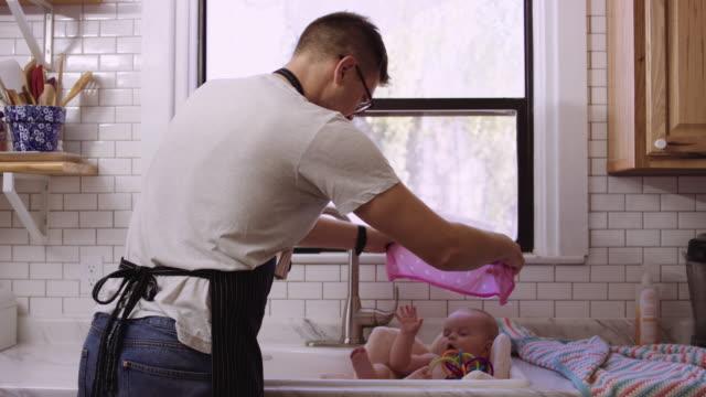 Milenaria de padre dando a su hija un baño fregadero - vídeo