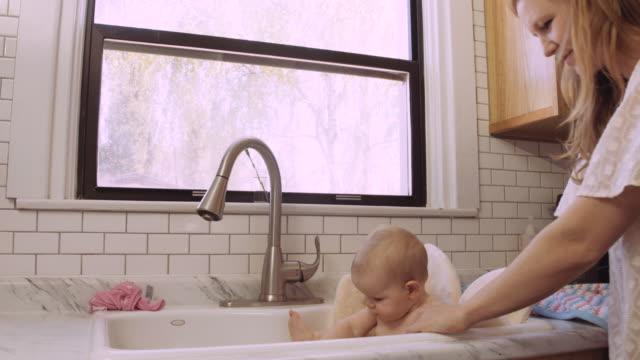 tusenåriga gamla mor att hennes dotter badkar handfat - baby bathtub bildbanksvideor och videomaterial från bakom kulisserna