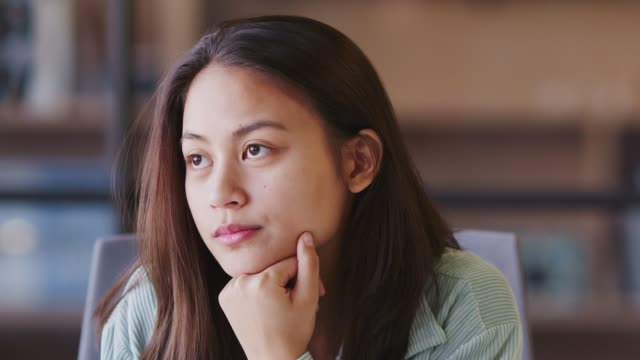 millennial asian female creative looking way in contemplation, resting chin on hand, close up - distrarre lo sguardo video stock e b–roll