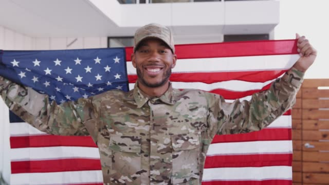 Millennial black male soldier steps towards camera holding US flag, smiling to camera, close up Millennial black male soldier steps towards camera holding US flag, smiling to camera, close up military uniform stock videos & royalty-free footage