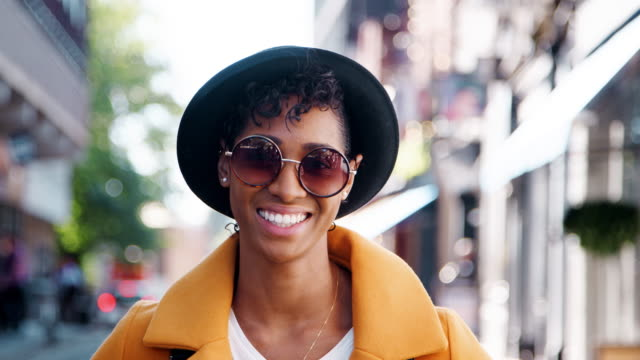 Millennial black woman wearing a yellow pea coat, sunglasses and a homburg hat, standing on a city street smiling to camera, close up