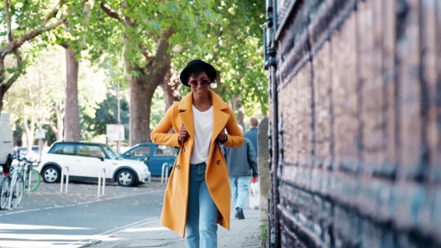 vídeos de stock, filmes e b-roll de mulher negra milenar, vestindo um casaco amarelo desabotoado e um chapéu de andar pelas ruas por trilhos, foco seletivo - camiseta preta