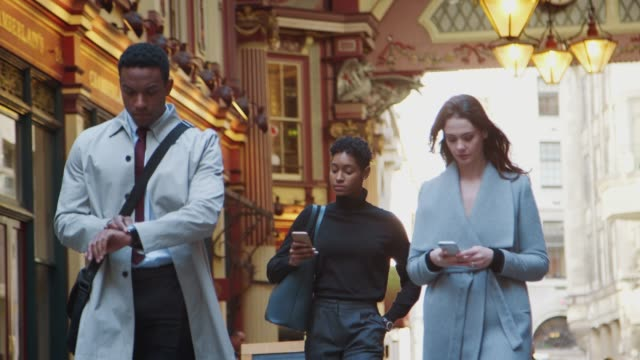 Millennial business people walking towards camera in Londonês historical Leadenhall covered street market, checking the time and using their phones, low angle