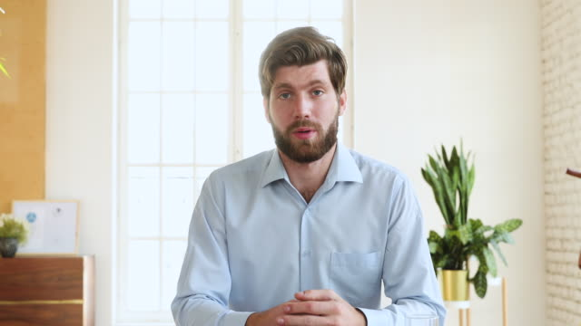vídeos de stock e filmes b-roll de millennial businessman talking to camera making conference video call - homens jovens