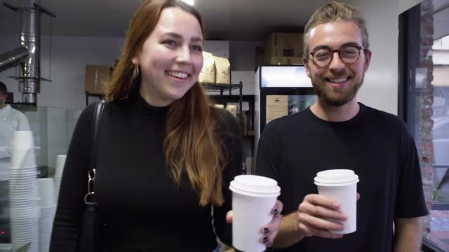 Millennial Couple Leaving a Neighborhood Coffee Shop Millennial couple enjoying themselves while leaving a local coffee shop. small business saturday stock videos & royalty-free footage