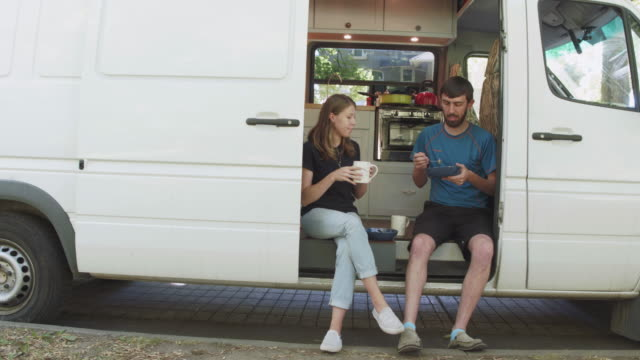 Millennial couple sitting in doorway of their van home A young couple who live in a van are sitting in the doorway while having breakfast rv interior stock videos & royalty-free footage