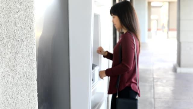 Millennial Half Japanese Woman Using ATM Machine at Bank