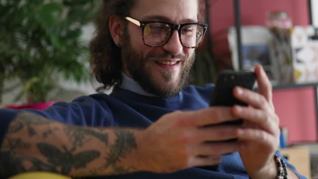 millennial man video chatting with friend - tatuaż filmów i materiałów b-roll