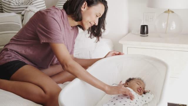 tusenden mor som sitter upp och letar efter sitt nyfödda barn som sover i en spjälsäng bredvid sängen - baby sleeping bildbanksvideor och videomaterial från bakom kulisserna