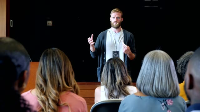 Millennial motivational speaker talks to large crowd during conference Young Caucasian conference or seminar keynote speaker gestures while motivating an audience. The audience listens attentively to the man's speech. speaker stock videos & royalty-free footage