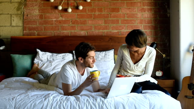 Millennial Multi Ethnic Couple in Bed with Laptop and Coffee video