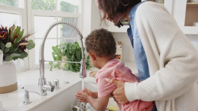 millennial mum standing at the kitchen sink helping her son wash his hands, side view, close up - ręczna kamera filmów i materiałów b-roll