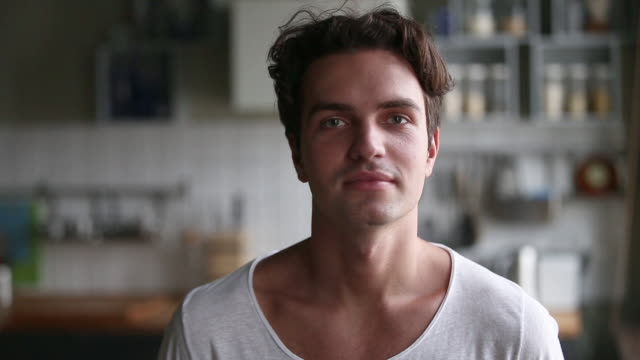 Millennial positive man posing at home in kitchen, video portrait