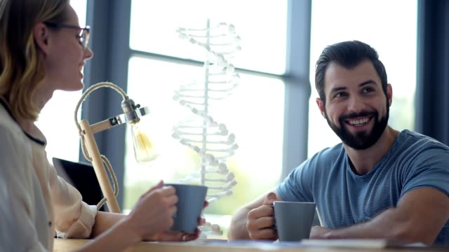 Millennial scientists drinking coffee during lunch break Rest is best. Selective focus on a bearded biologist talking to his colleague while booth drinking coffee and sitting next to a three dimensional DNA model. biosensor stock videos & royalty-free footage