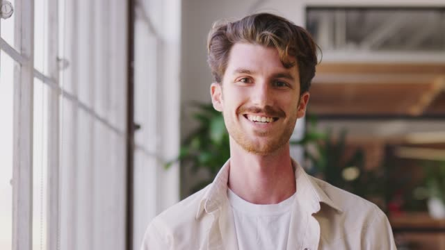 Millennial white male creative standing in office, turning and smiling to camera, close up