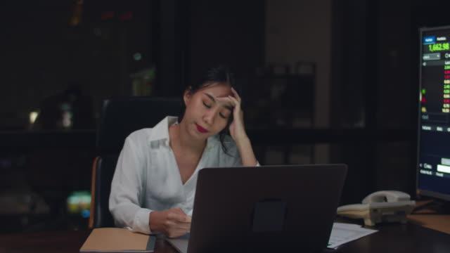stockvideo's en b-roll-footage met millennial jonge chinese onderneemster werk late night stress uit met project onderzoek probleem op laptop in vergaderruimte op klein modern kantoor. - oost azië