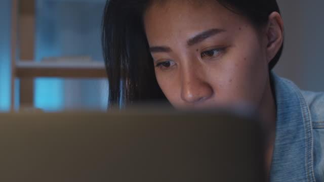 millennial unga kinesiska affärskvinna som arbetar sent på kvällen stress ut med projektet forskningsprojekt problem på laptop i vardagsrummet i moderna hem. - stress bildbanksvideor och videomaterial från bakom kulisserna