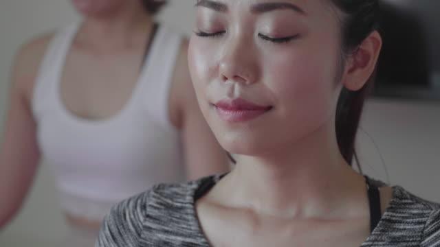 ヨガのクラスで呼吸の抜粋で瞑想するミレニアル世代の女性 - スタジオ 日本人点の映像素材/bロール
