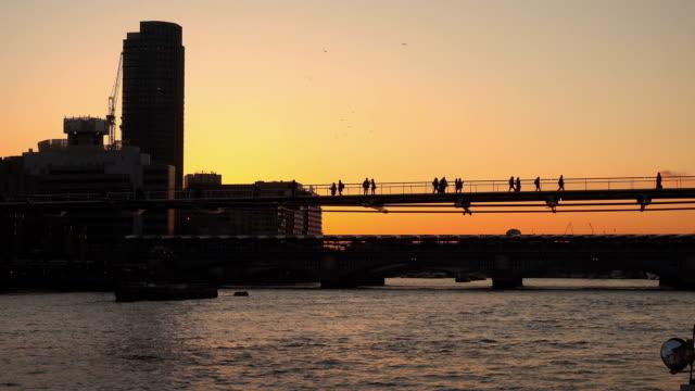 millennium bridge in the backlight at sunset - inghilterra sud orientale video stock e b–roll