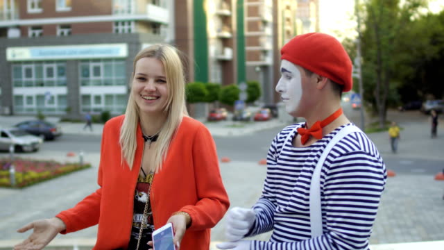 mime and young girl has fun at fountain background - гримировальные краски стоковые видео и кадры b-roll