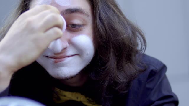 mime applying white paint on his face - гримировальные краски стоковые видео и кадры b-roll