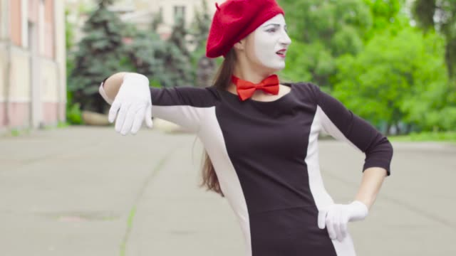 Mime girl leaned against the invisible wall Two women mimes in black and white dress do performance in the city. Actress leans on an invisible support and imitate rest, chill. Performance of street artist greasepaint stock videos & royalty-free footage