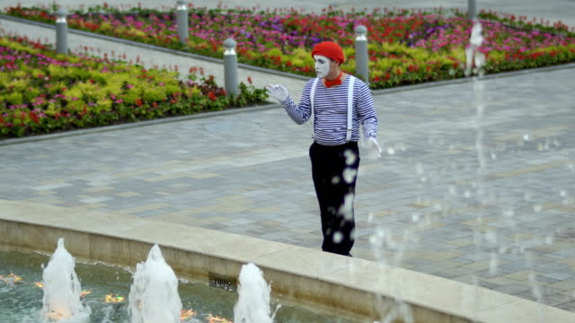 Mime in red beret has fun with fountains Funny mime in red beret has a performance at fountain background and moving his hands as a conductor. Man wearing stripped shirt is an street actor and playing funny scenes for people. greasepaint stock videos & royalty-free footage