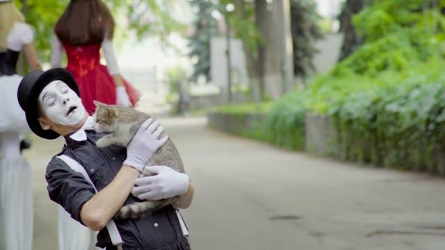 mime joking with cat on the street - гримировальные краски стоковые видео и кадры b-roll