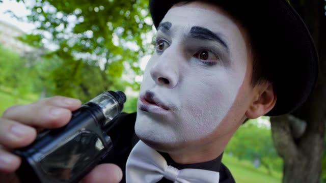 stockvideo's en b-roll-footage met mime rookt elektronische sigaret - vetschmink