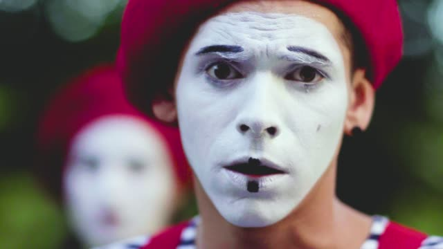 Mimes crooking face in funny ways Male and female mimes in red hats, white face and striped clothes do funny moves with face. Actor move eyebrowes and mimic muscles, his colleague behind man's back trying to imitate him. Actors have fun and joking. Performance of street artists actor stock videos & royalty-free footage