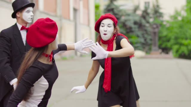 Mimes is crooking in the city Company of three mimes, man and women in black dress do perfomance in the city. Girls actors is trying hard to catch each other hands, whan they do it ladies make sigh of relief and relax. Man mime shows his dissatisfy. Performance of street artists greasepaint stock videos & royalty-free footage